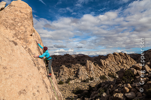 Elaina Arenz, co-owner Chicks Climbing and Skiing, applying just the right amount of pressure in the amazing and surreal, Joshua Tree, California. ©Greg Epperson