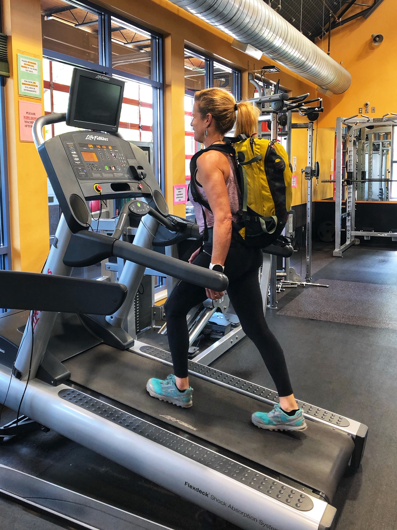 Carolyn Parker, training for alpine climbing by wearing a pack on an inclined treadmill