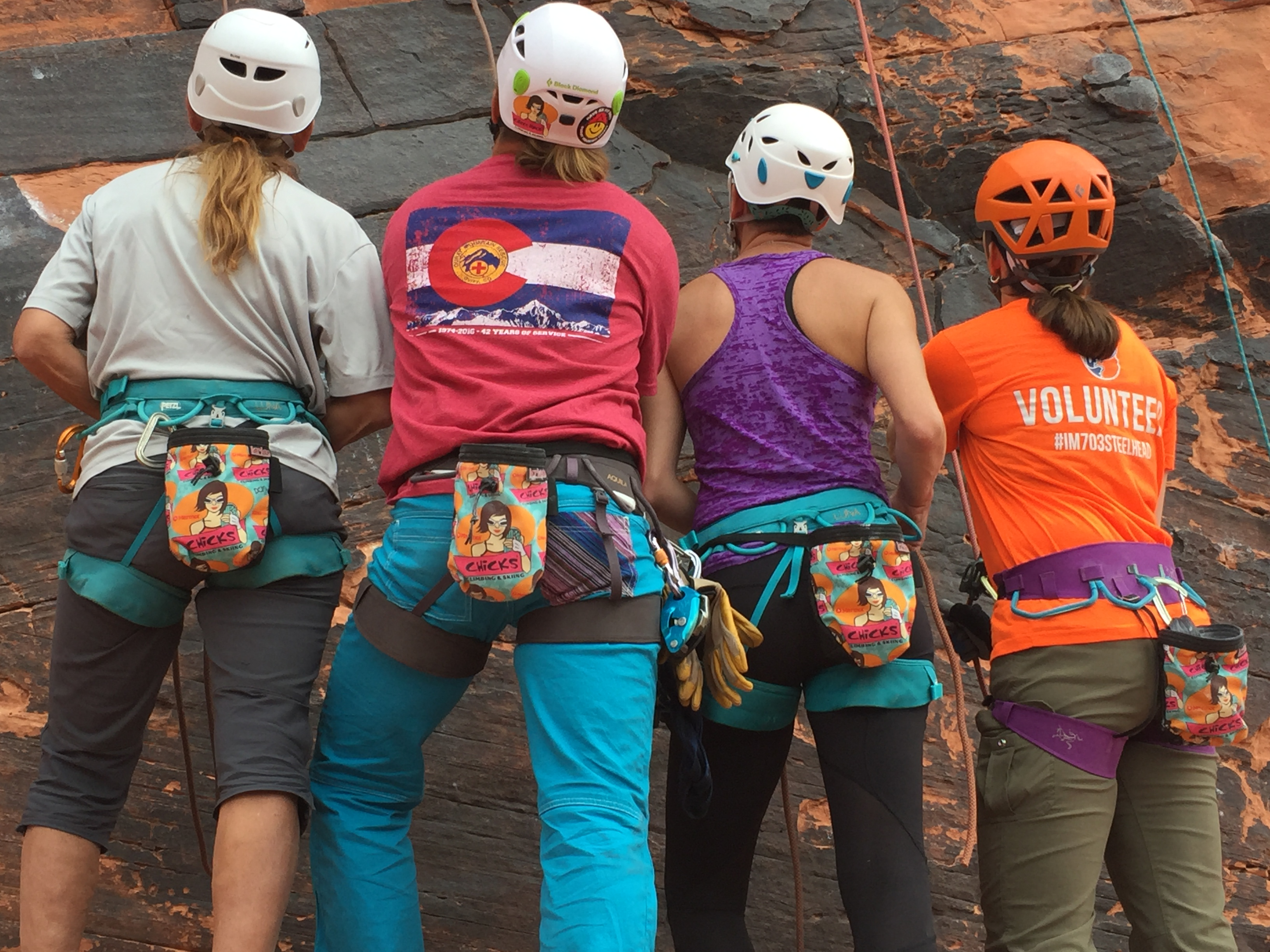 Find more climbing partners at a Chicks Climbing clinic. 4 Chicks participants lined up to show off their Chicks chalk bags